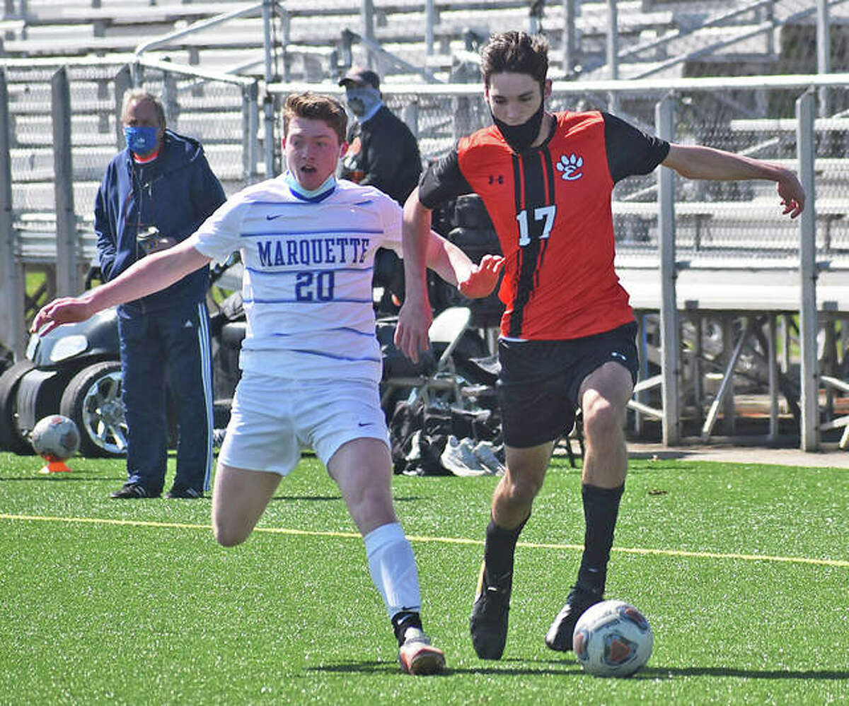 Edwardsville's Brennan Weller (right) and Marquette Catholic's Jacob Morris race down the field for possession of the ball during the first half on Saturday in Edwardsville.