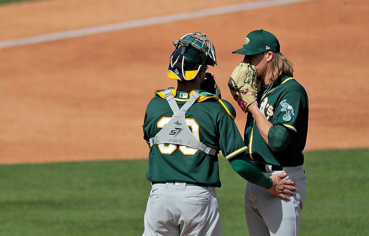 Austin Allen (30) talks with Jordan Weems (70) in the third inning as the Oakland Athletics played the Colorado Rockies at Salt River Fields at Talking Stick in Scottsdale, Ariz., on Wednesday, March 3, 2021.
