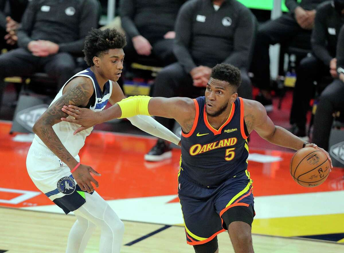 Kevon Looney (5) dribbles around Jaden McDaniels (3) in the first half as the Golden State Warriors played the Minnesota Timberwolves at Chase Center in San Francisco, Calif., on Monday, January 25, 2021.