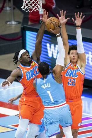 Houston Rockets guard John Wall (1) shoots over Oklahoma City Thunder forward Luguentz Dort (5) and Oklahoma City Thunder center Isaiah Roby (22) during the first quarter of an NBA game between the Houston Rockets and Oklahoma City Thunder on Sunday, March 21, 2021, at Toyota Center in Houston, TX. Photo: Mark Mulligan, Staff Photographer / © 2021 Mark Mulligan / Houston Chronicle