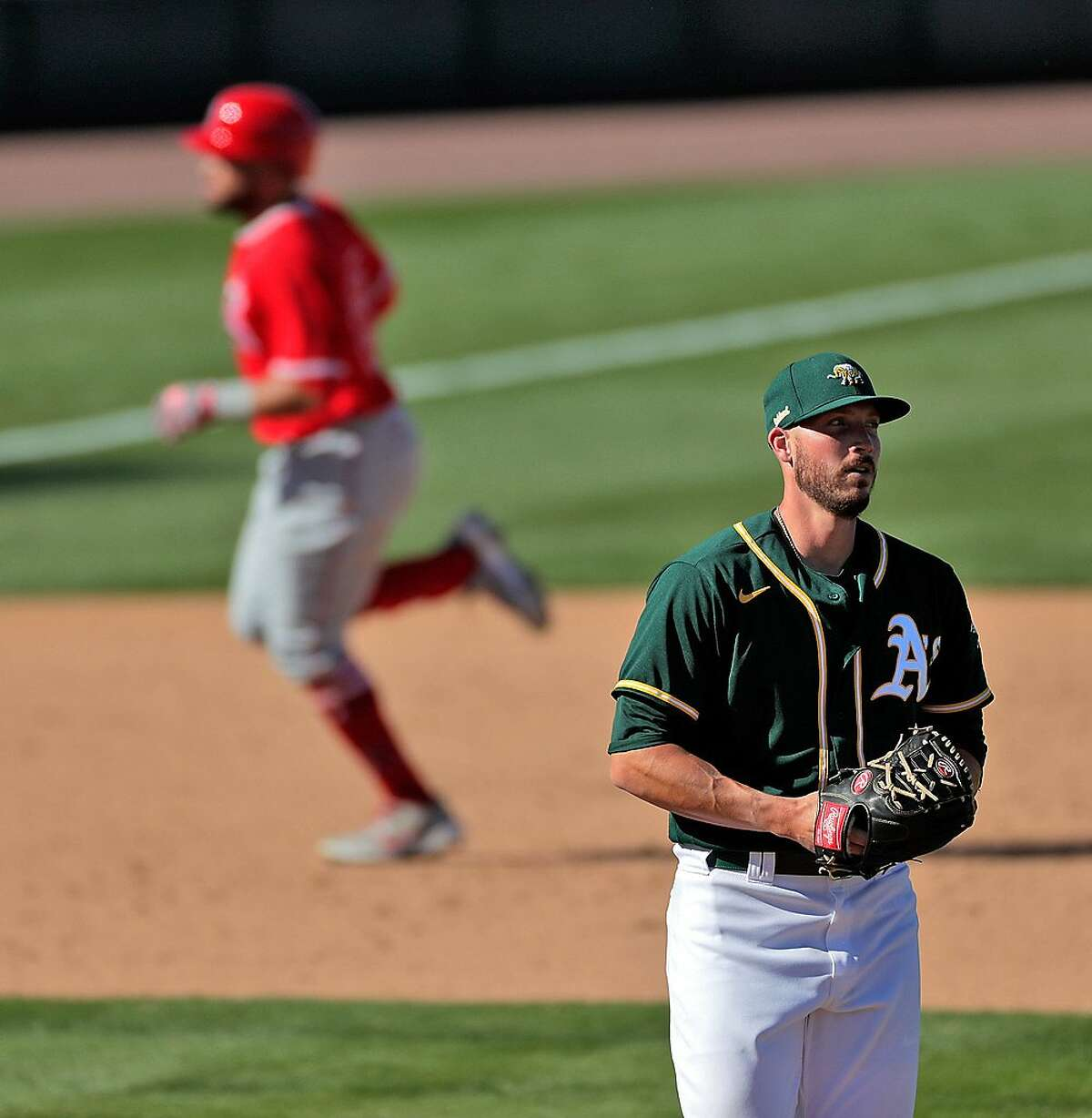 Nik Turley (23) walks back to the mound as Jose Rojas (23) rounds the bases after a solo homerun in the seventh inning as the Oakland Athletics played the Los Angeles Angels at Hohokam Stadium in Mesa, Ariz., on Friday, March 5, 2021.