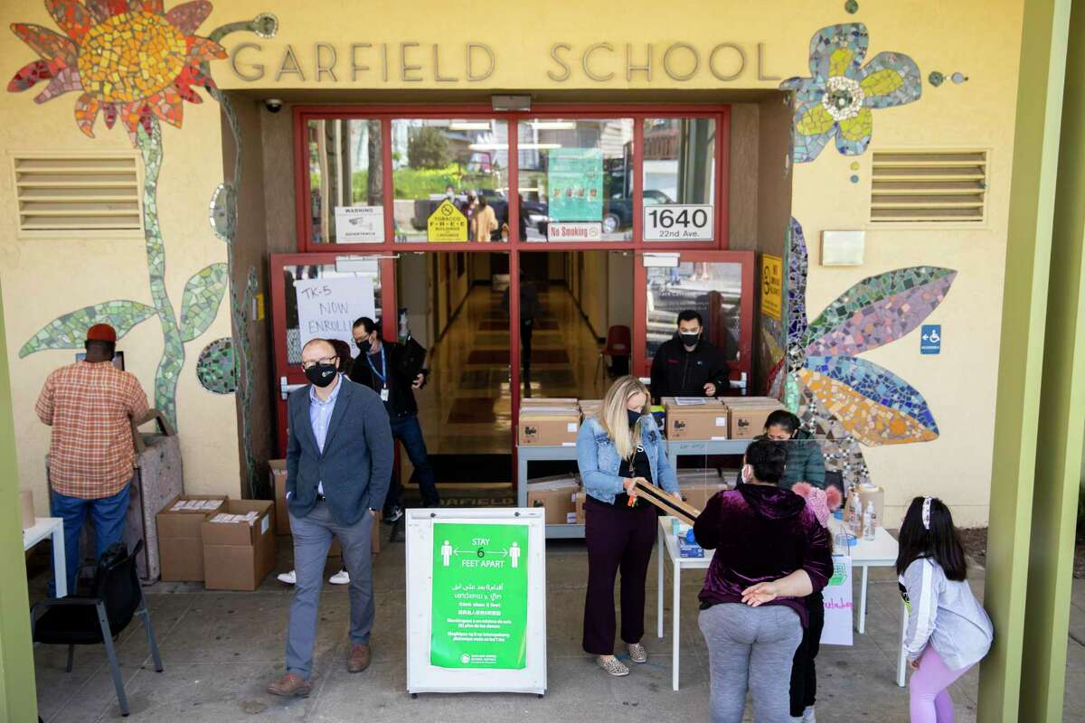 Parents and students arrive outside of Garfield Elementary School in Oakland this month to receive their laptops for distance learning.