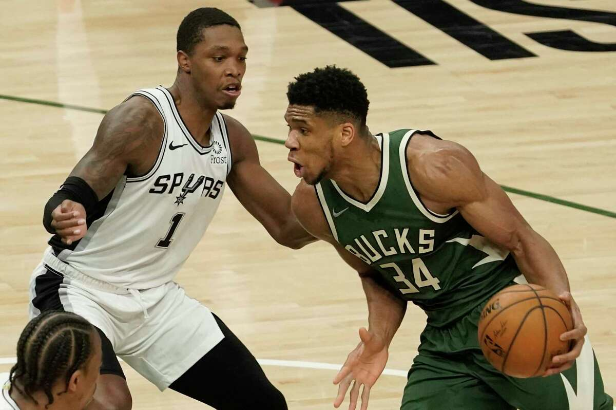 Milwaukee Bucks' Giannis Antetokounmpo tries to drive past San Antonio Spurs' Lonnie Walker IV during the first half of an NBA basketball game Saturday, March 20, 2021, in Milwaukee. (AP Photo/Morry Gash)
