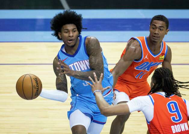Houston Rockets guard Kevin Porter Jr. (3) passes around Oklahoma City Thunder center Moses Brown (9) during the third quarter of an NBA game between the Houston Rockets and Oklahoma City Thunder on Sunday, March 21, 2021, at Toyota Center in Houston, TX. Photo: Mark Mulligan, Staff Photographer / © 2021 Mark Mulligan / Houston Chronicle