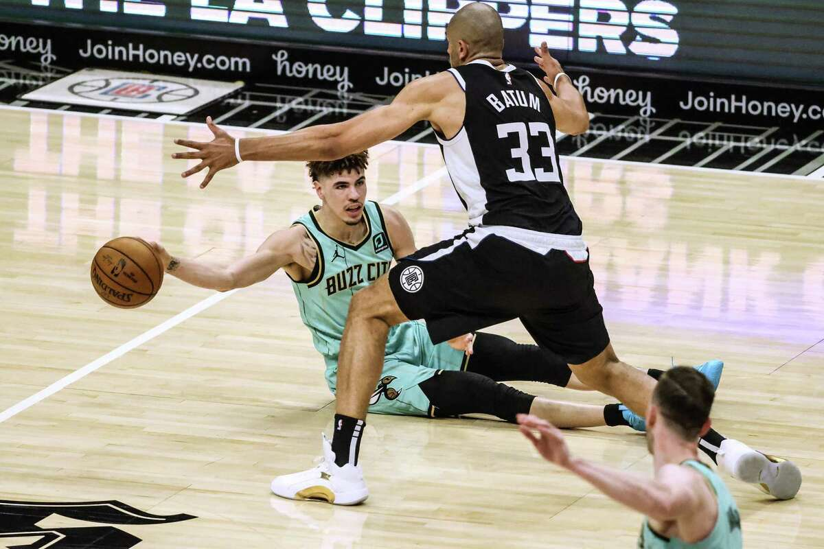 The Charlotte Hornets' LaMelo Ball (2) passes the ball to teammate Gordon Hayward, bottom right, as the Los Angeles Clippers' Nicolas Batum (33) defends during first-half action at Staples Center in Los Angeles on Saturday, March 20, 2021. (Robert Gauthier/Los Angeles Times/TNS)