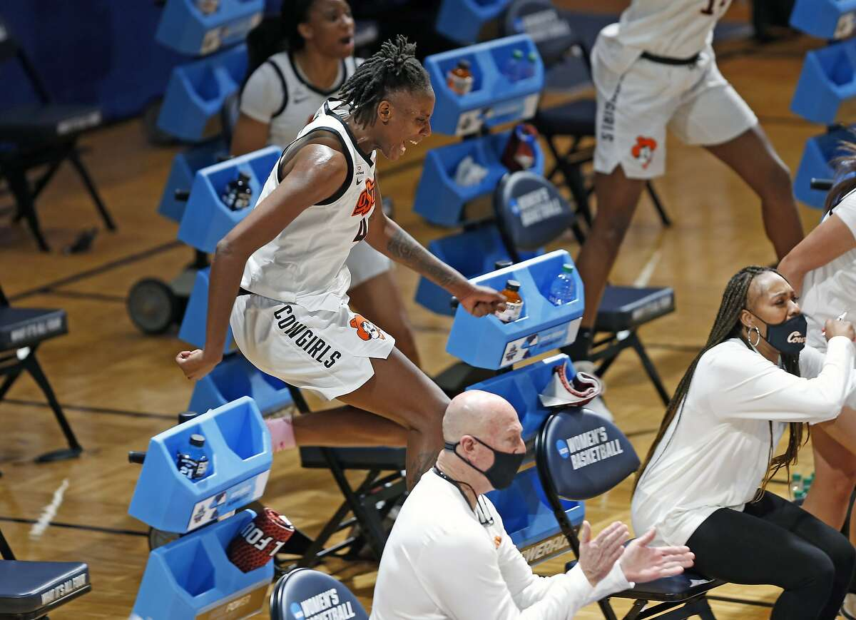 Oklahoma State forward Natasha Mackleaps over chairs to cheer a basket by reserves Sunday in San Antonio, Texas.