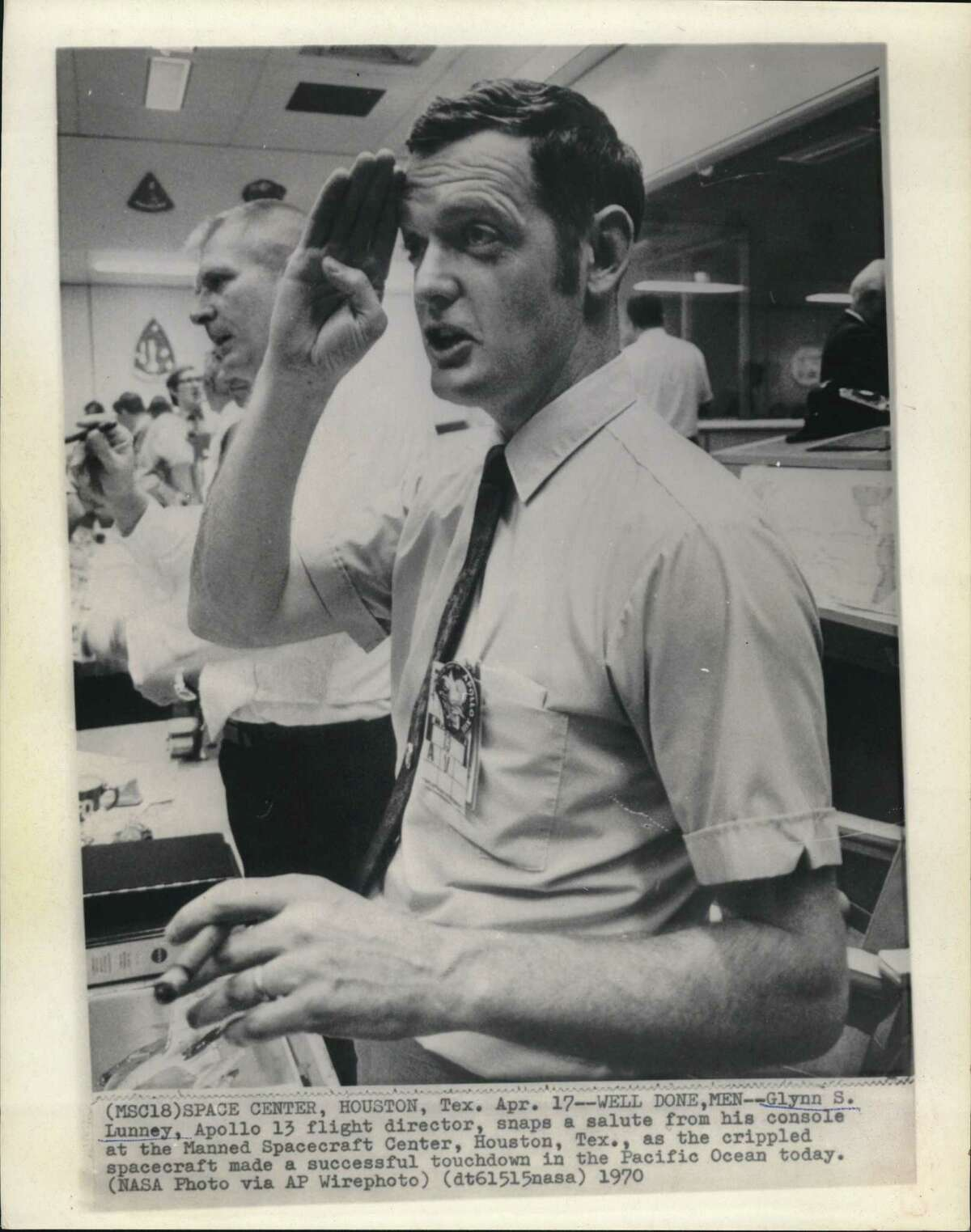 Space Center, Houston, TX: Glynn S. Lunney, Apollo 13 flight director, snaps a salute from his console at the Manned Spacecraft Center, Houston, Texas, as the crippled spacecraft made a successful touchdown in the Pacific Ocean today.