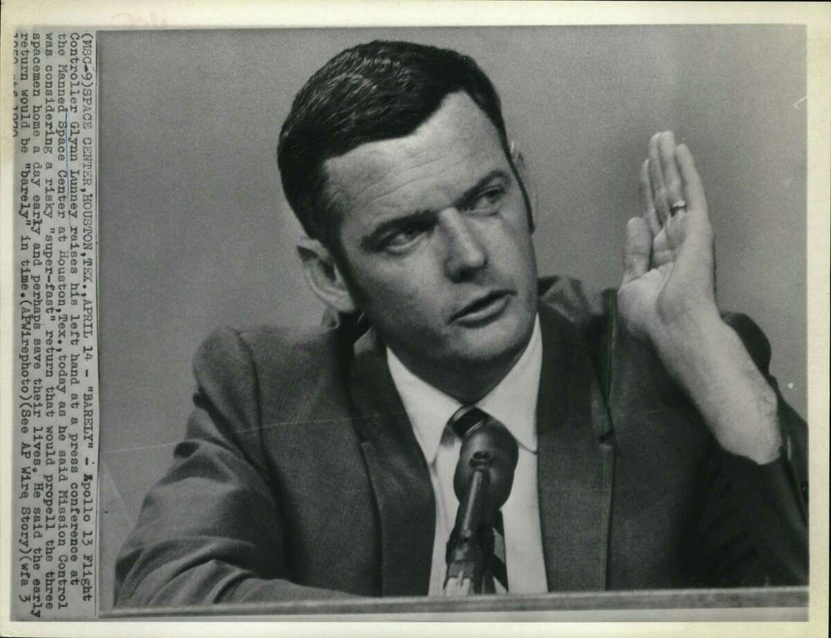 """Space Center, Houston, TX: Apollo 13 Flight Controller Glynn Lunney raises his left hand at a press conference at the Manned Space Center at Houston, Texas, today as he said Mission Control was considering a risky """"super-fast"""" return that would propel the three spacemen home a day early and perhaps save their lives. He said the early return would be """"barely"""" in time."""