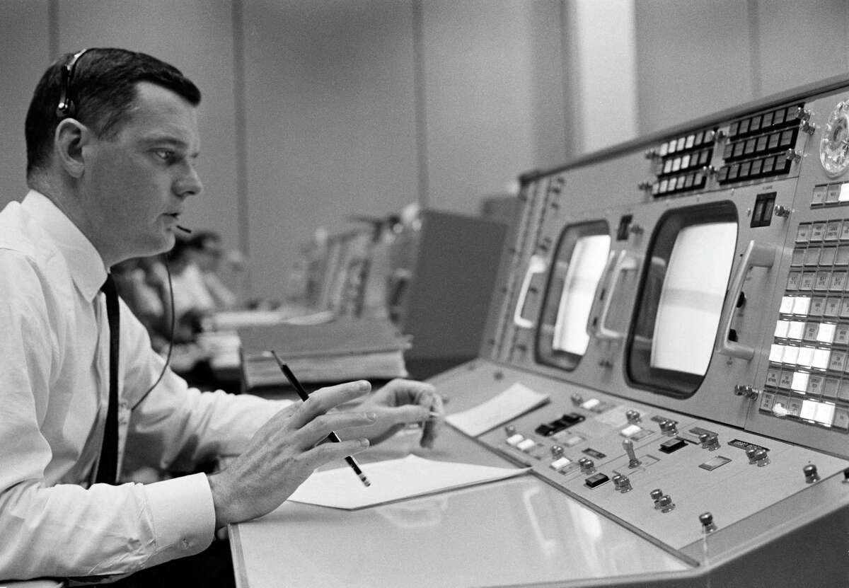Glynn S. Lunney is shown in 1965 at his console in the Mission Control Center during an Apollo simulation exercise.