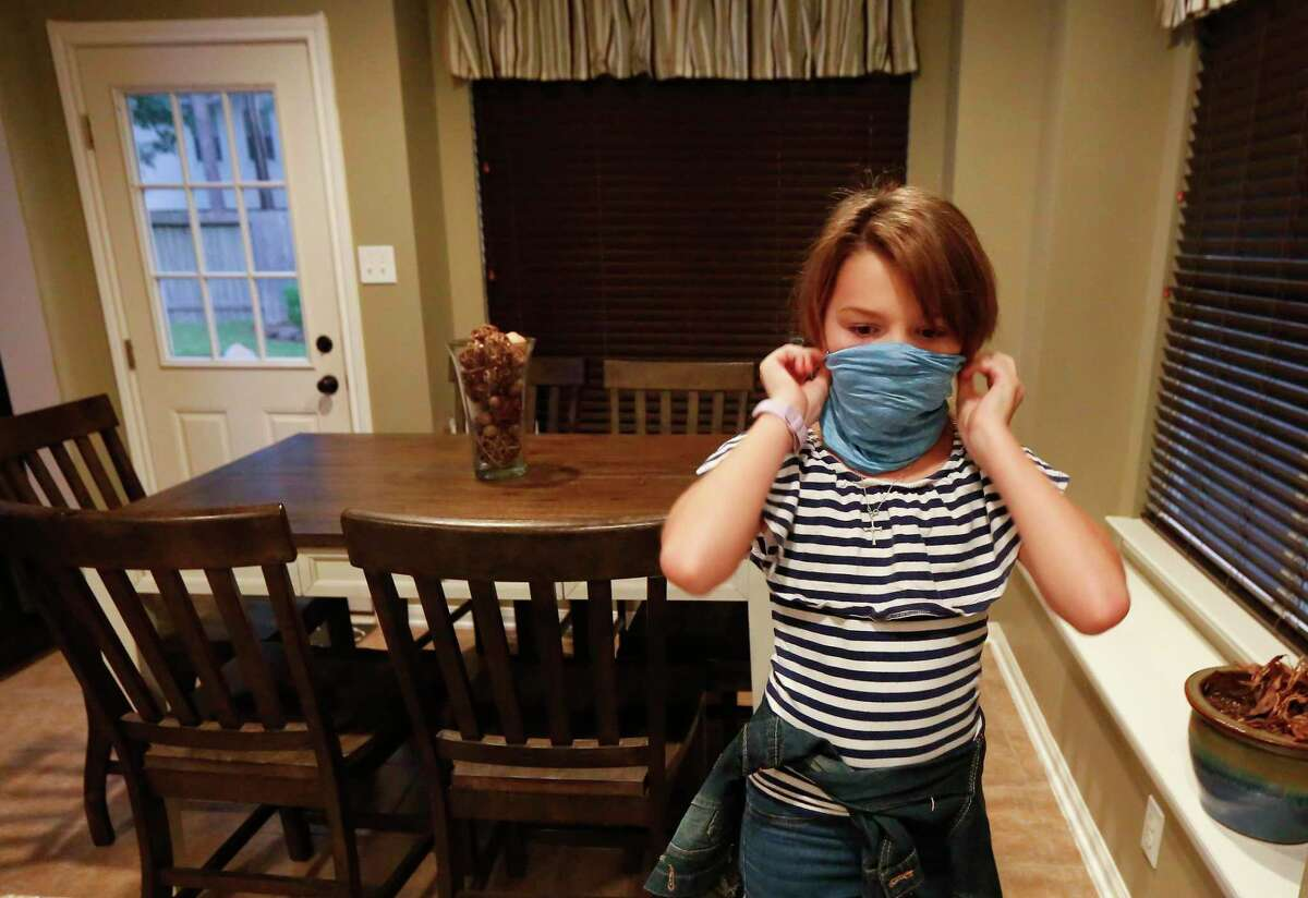 Fifth-grade Allie Stidham makes sure her mask fits well Monday, Aug. 24, 2020, in Humble before school.