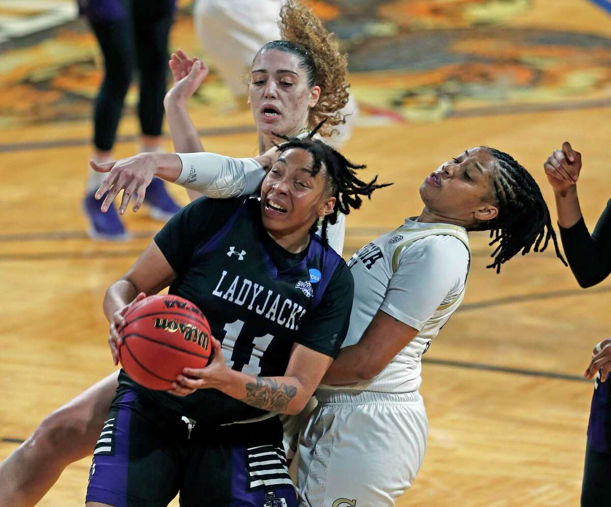 Stephen F. Austin forward Avery Brittingham (11) battles Georgia Tech defenders during the second half of a college basketball game in the first round of the women's NCAA tournament at the Greehey Arena in San Antonio, Texas, Sunday, March 21, 2021. (AP Photo/Ronald Cortes)
