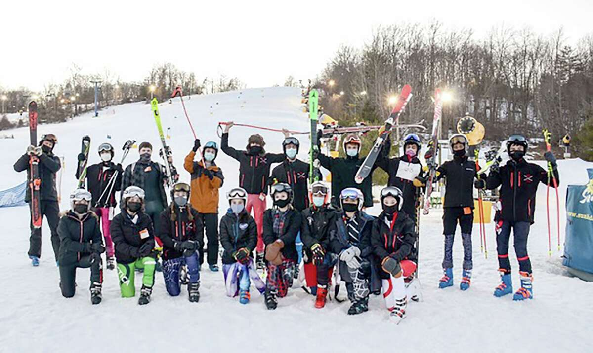 The New Canaan skiers celebrate their state championship qualification following a regular season meet on Tuesday, March 9, 2021. From left are, front row, Charlotte Strathmann, Luisa Strathmann, Captain Natalie Fuhr, Kailin Downey, Rory McCarthy, Paxton Beladino, Lissette Jimenez, and Ella Schwartz; back row, coach Chandler Brill, Amelie L'Henaff, Phillip Ettinger, David Smith, Josh Snelwar, Myles Gropper, Austin Grillo, Hari Roshi, Will Stallings and Braydon Bavoso.