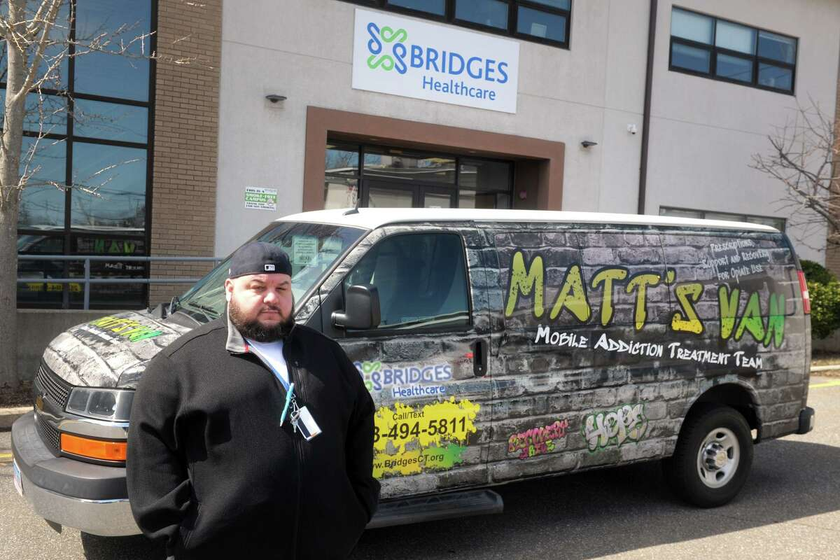 Chris Cavaliere, recovery services specialist with Bridges Healthcare, in front of the Mobile Addiction Transition Team's van in Milford.