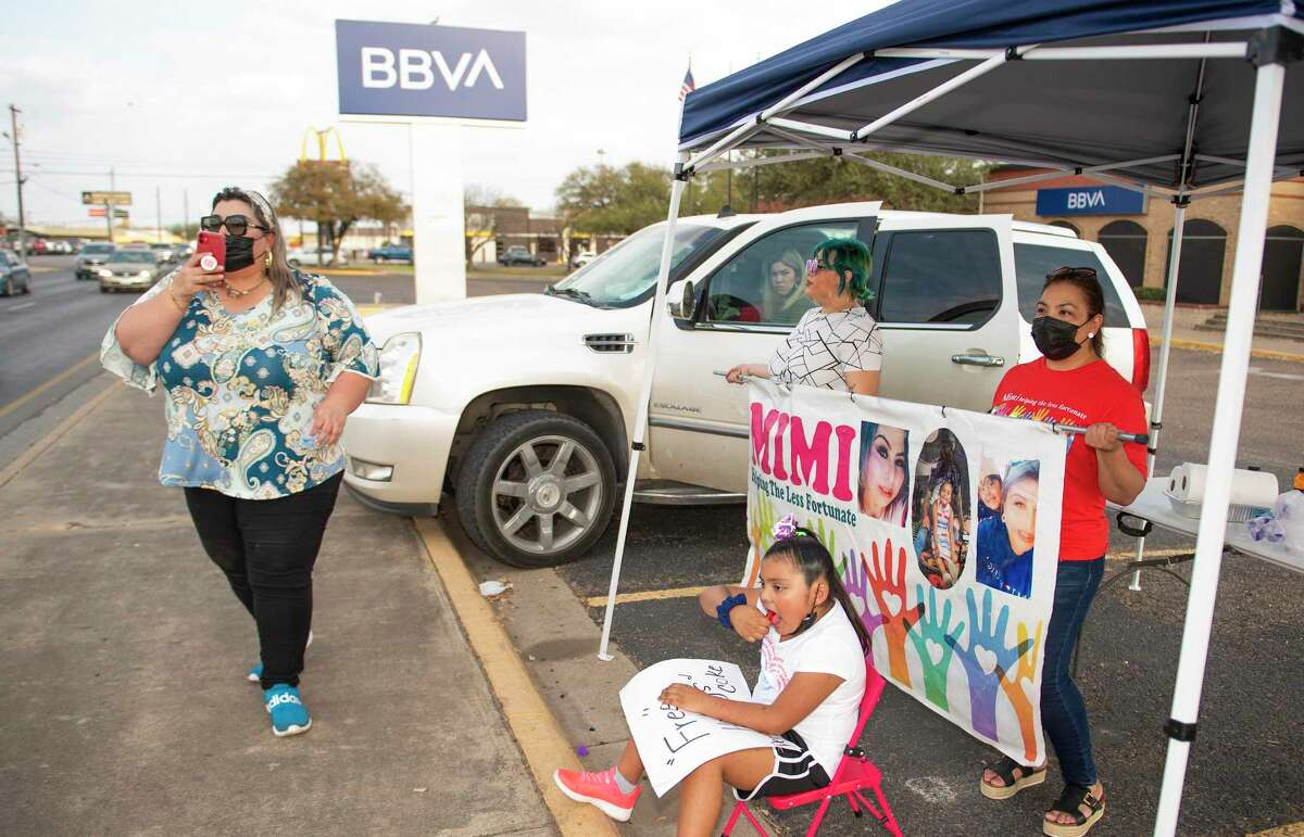 Mimi Espinoza broadcasts on Facebook Live to announce the free food distribution by MIMI Helping The Less Fortunate Friday, Mar. 12, 2021, outside BBVA bank's Guadalupe Street location.