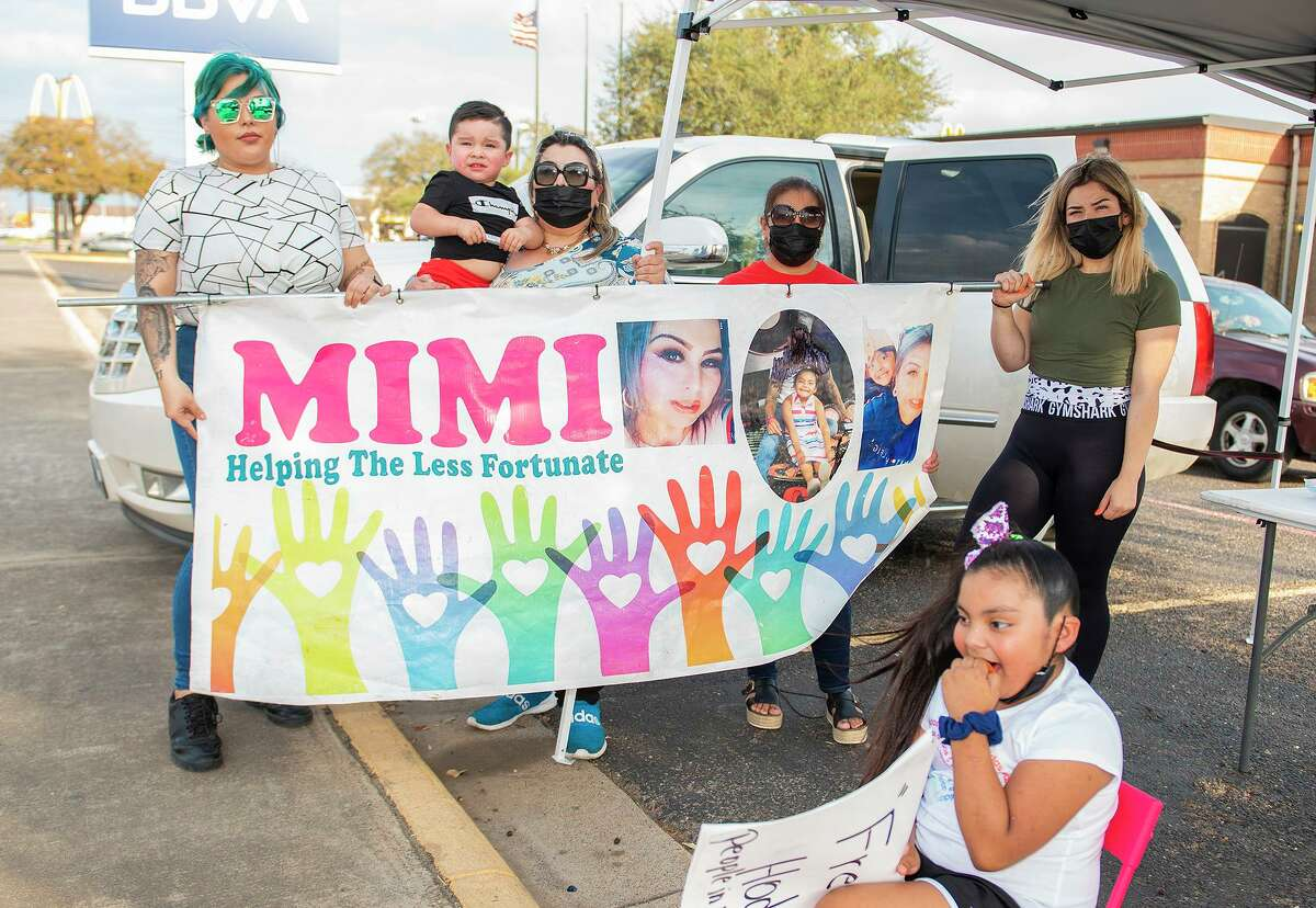 """Ashley Espinoza, Jasper Cruz, Juanita """"Mimi"""" Melendez, Elvira Almanza, Marcy Espinoza and Kaitlyn Espinoza gather for a photo March 12, 2021, after arriving outside BBVA bank's Guadalupe Street location for a food distribution by Mimi Helping The Less Fortunate."""