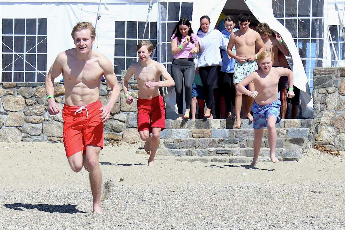 Participants race to the water to take part in the Depot Dip at Wee Burn Beach Club on Sunday, March 21, 2021.
