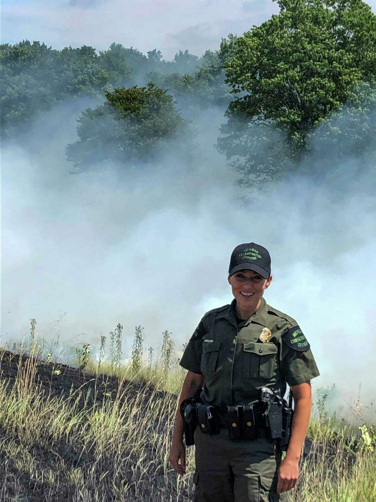 Michigan Conservation Officer Angela Greenway stands in front of smoke from an extinguished wildfire along US-131 that she responded to in 2019. (Courtesy photo/Michigan Department of Natural Resources)