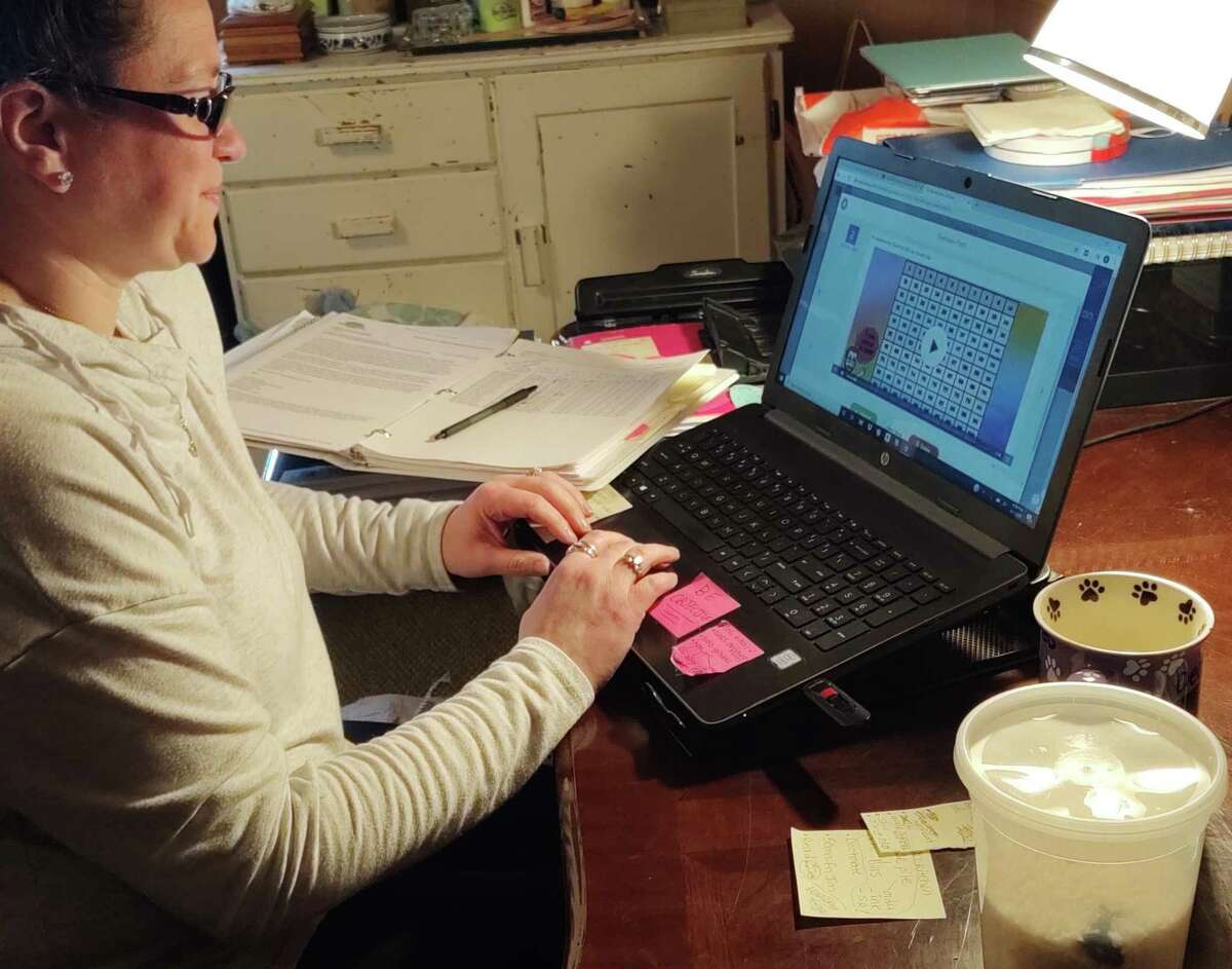 Kimberly Atkinson, kindergarten teacher at Booth Hill School, correcting a student's SEESAW assignment for the day.