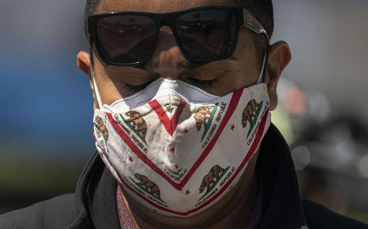 Mark Gonzalez wears a California-themed mask as he participates in a car caravan rally to denounce hate against the Asian American and Pacific Islander communities in Los Angeles on March 19, 2021.