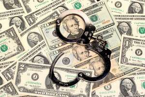 a pair of open handcuffs sitting on top of a pile of us dollars of assorted denominations