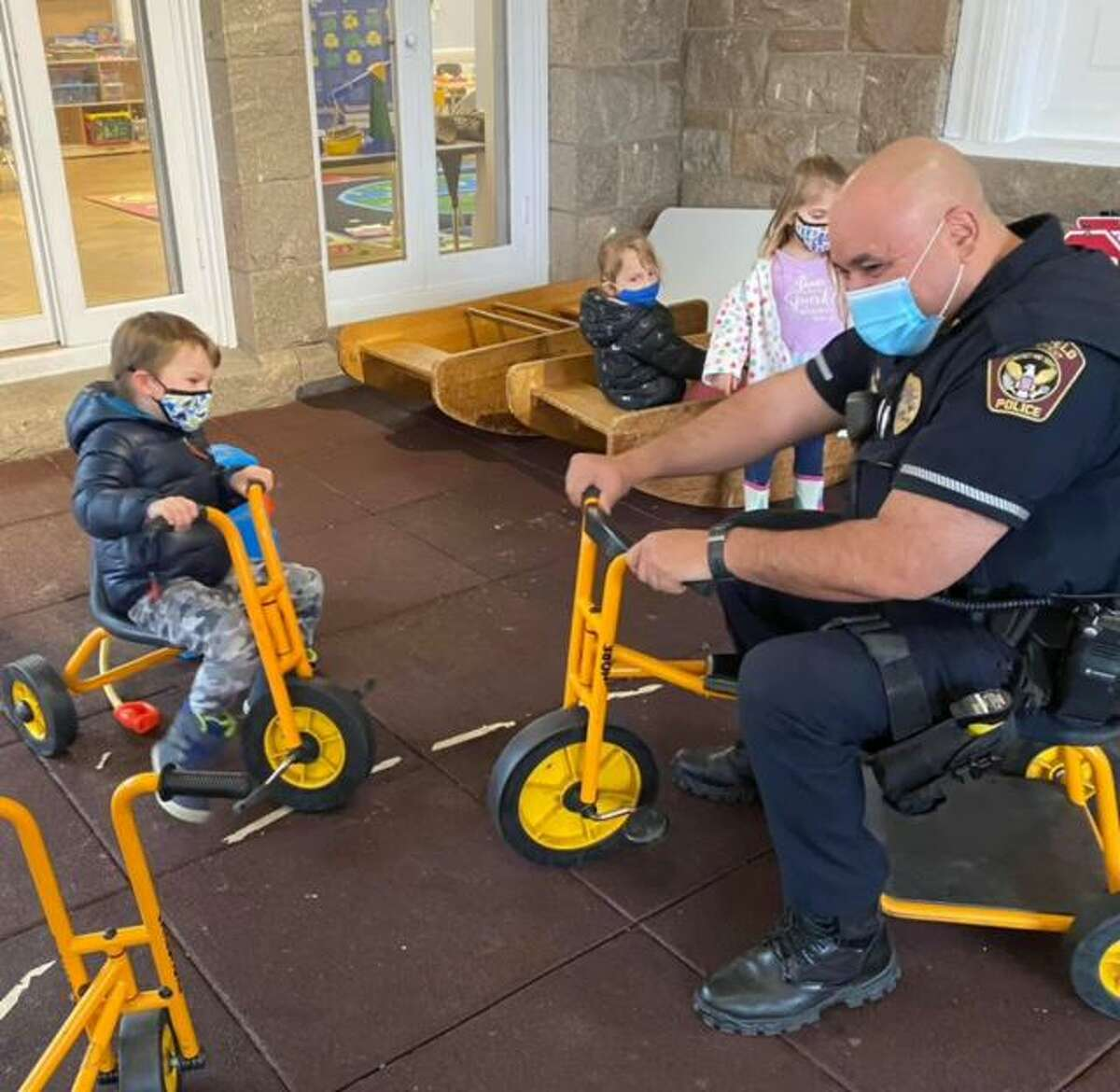 Ridgefield Police Officer Luis Caba rides a student bicycle at the Jesse Lee Day School while giving a safety talk to the children on March 18, 2021.