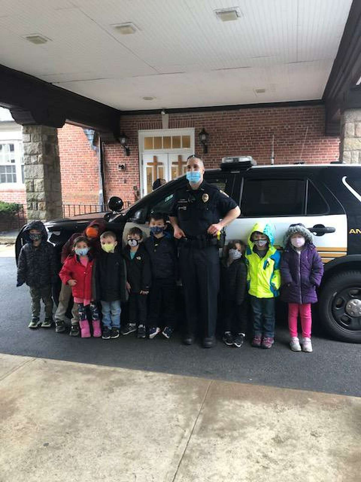 Ridgefield Police Officer Anthony McMahon stands with a group of children at the Jesse Lee Day School after giving a safety talk on March, 18, 2021.