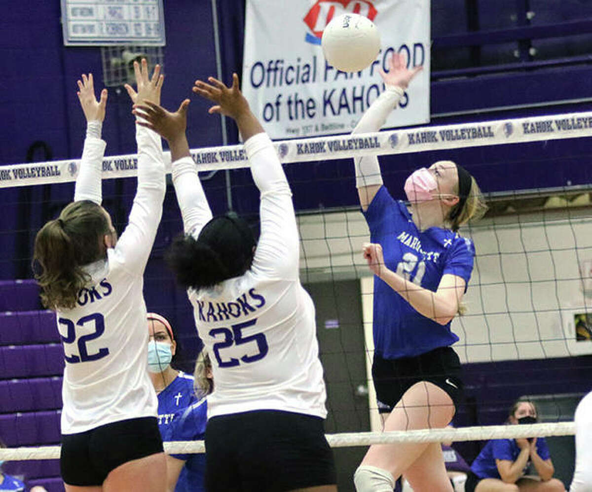 Marquette Catholic's Emma Menke hits over the block by Collinsville's Katie Dawson (22) and Kennedy Fisher (25) during the season opener last Wednesday at Fletcher Gym in Collinsville.