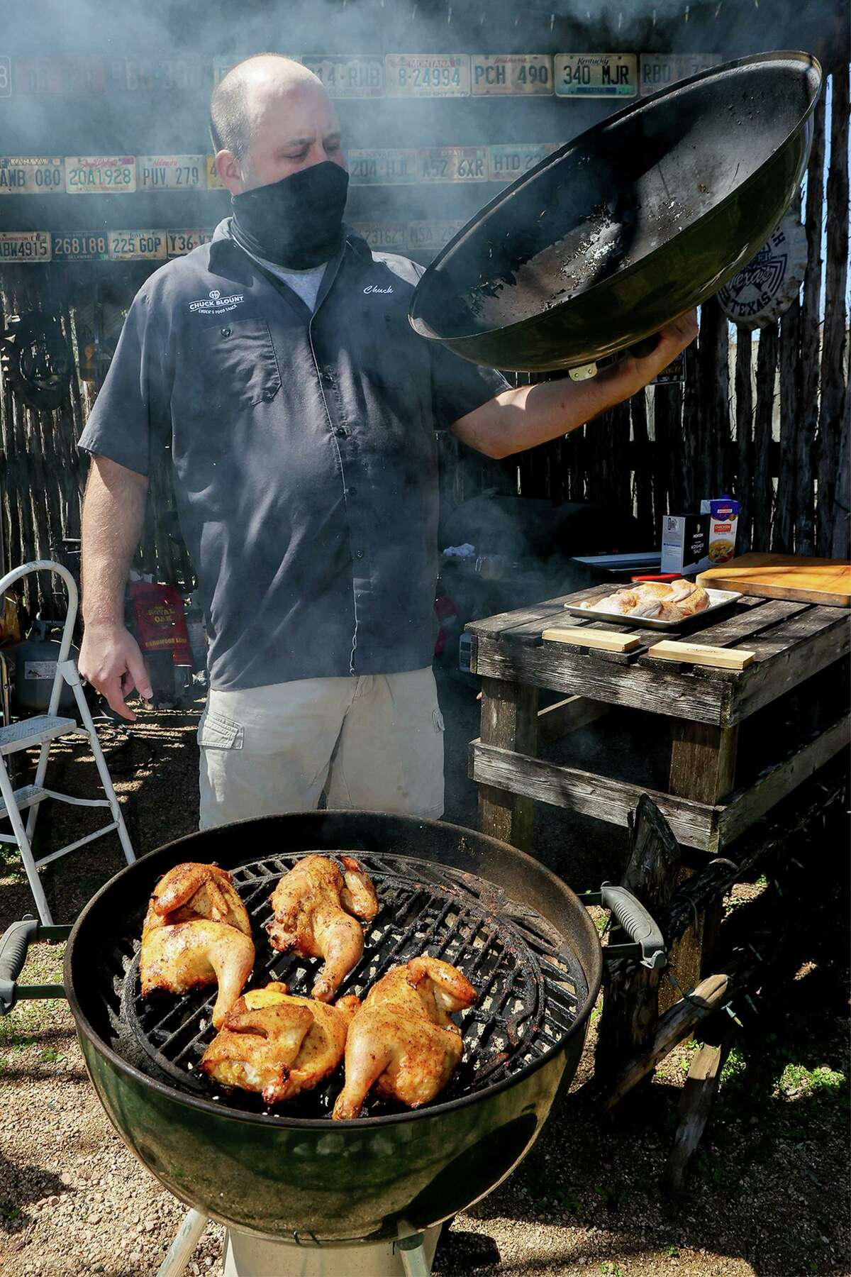 Chuck Blount takes the lid off the grill prior to comparing taste and texture of various ways to cook chicken.