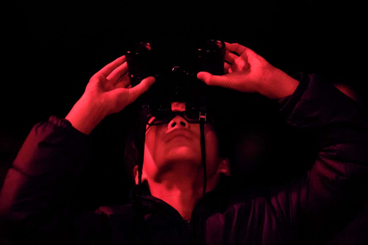 A boy uses binoculars to observe the Moon at the George Observatory in the Brazos Bend State Park.