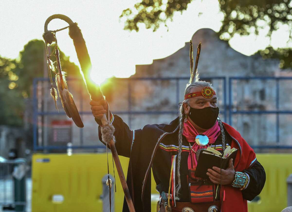 Papabear, the artist Isaac Cardenas Cona of the Tap Pilam Coahuiltacan Nation leads a prayer during their 25th annual sunrise ceremony and run in front of the Alamo Saturday morning to honor ancestors buried inside the Shrine of Texas.