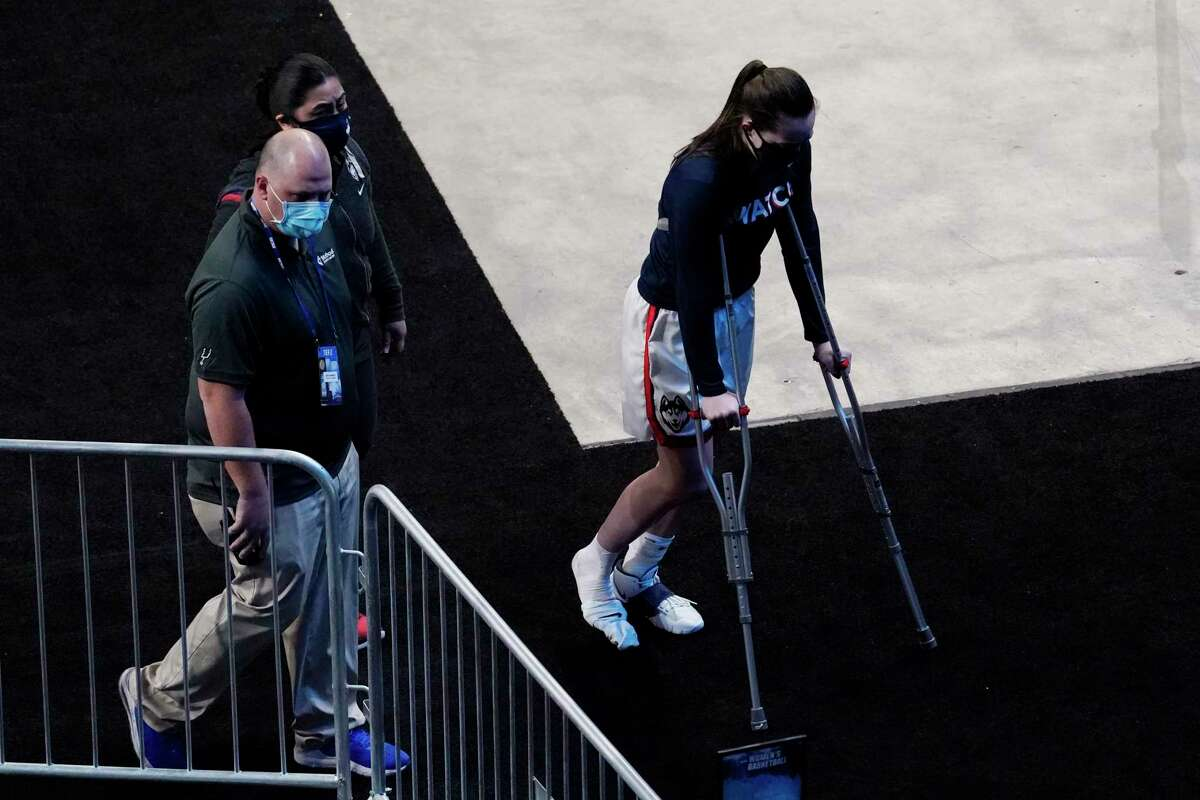 UConn guard Nika Muhl, right, leaves the arena floor on crutches after an injury during the first half of a college basketball game against High Point in the first round of the women's NCAA tournament at the Alamodome in San Antonio, Sunday, March 21, 2021. (AP Photo/Eric Gay)