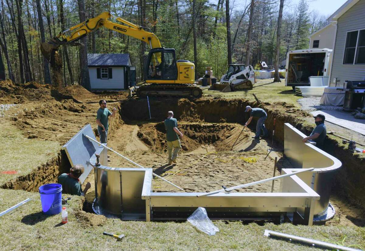 The inground pool crew with Alpin Haus works installing the galvanized steel walls of a pool at a home on Monday, March 22, 2021, in Saratoga Springs, N.Y. This is the very first pool of the season that the crew is building. (Paul Buckowski/Times Union)