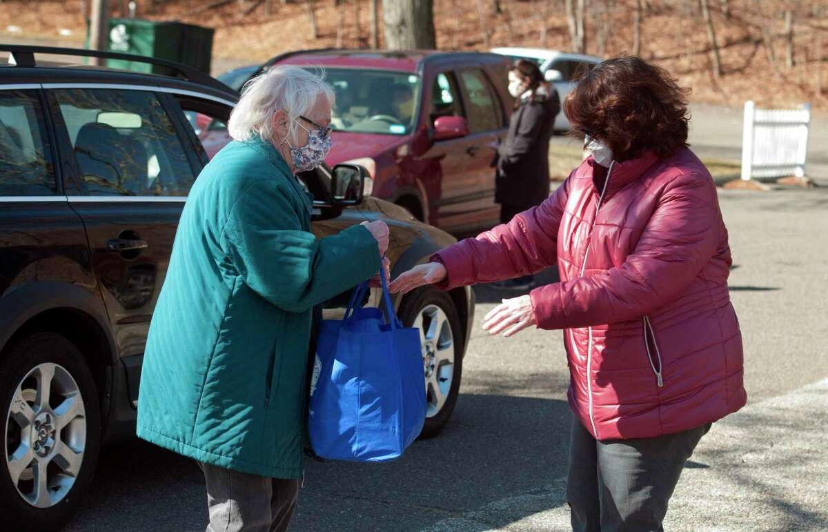 Gail Schoennagel, left, hands off a bag of donated food to Huntington Congregational Church Pastor Lucille L. Fritz during a drive-thru food collection at the church in Shelton, Conn., on Saturday Mar. 20, 2021. The collected food goes to the Valley Food Bank at Spooner House.