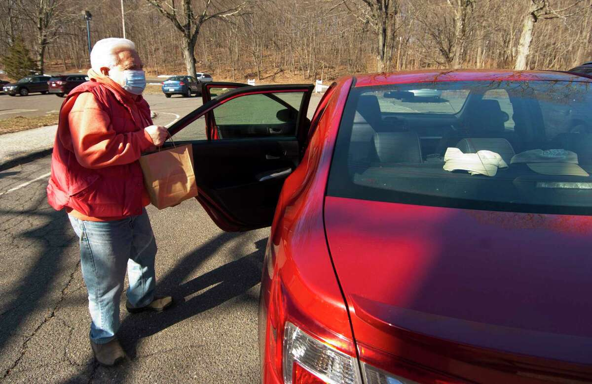 Bob Sembera donates a bag of food during Huntington Congregational Church's drive-thru food collection in Shelton, Conn., on Saturday Mar. 20, 2021. The collected food goes to the Valley Food Bank at Spooner House.