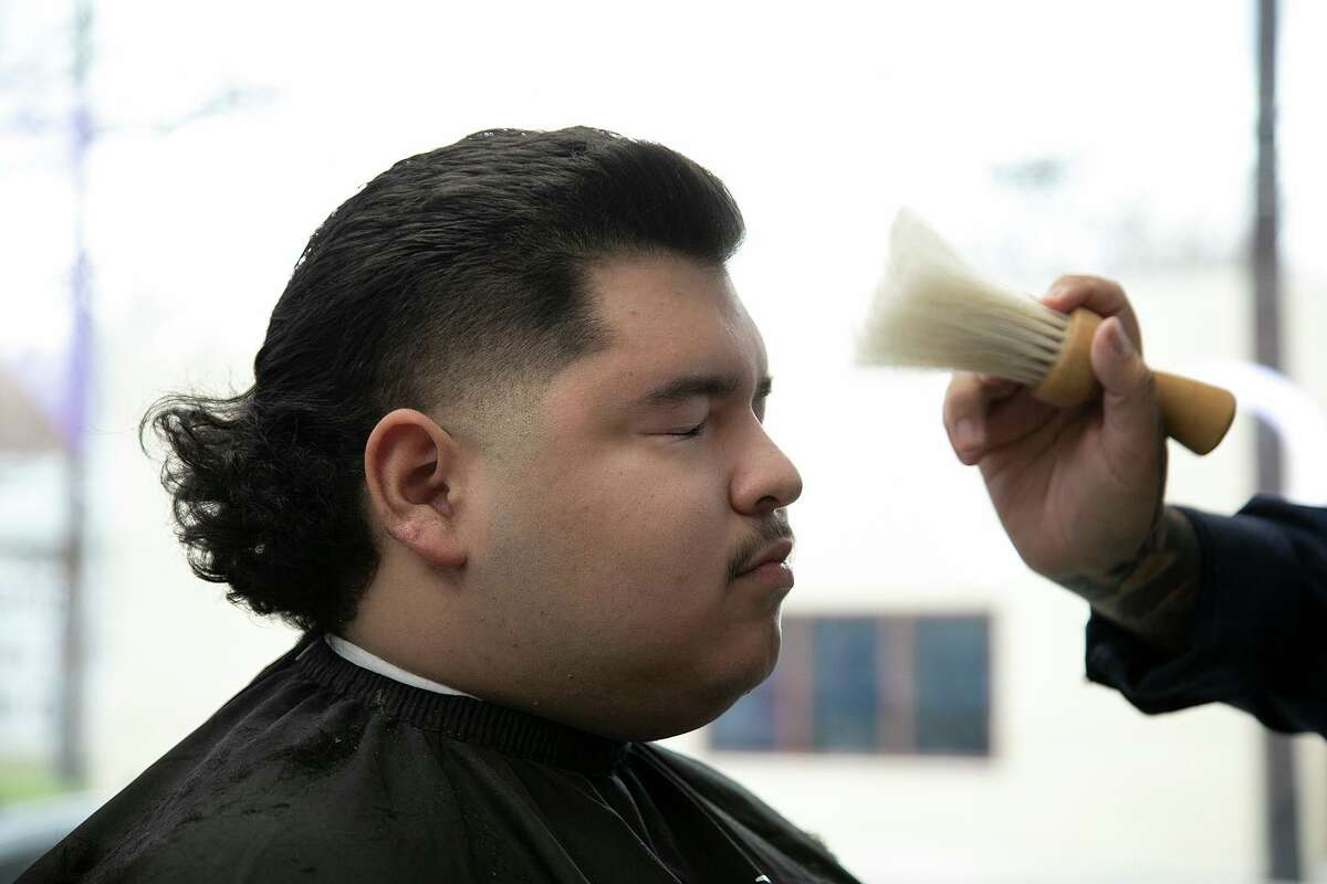 Jonné Jasso brushes hair off the face of Cristian Muñiz after his haircut at Pinstripes Classic Barber Shop.