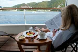 A cruise ship passenger relaxes while reading the paper over coffee.