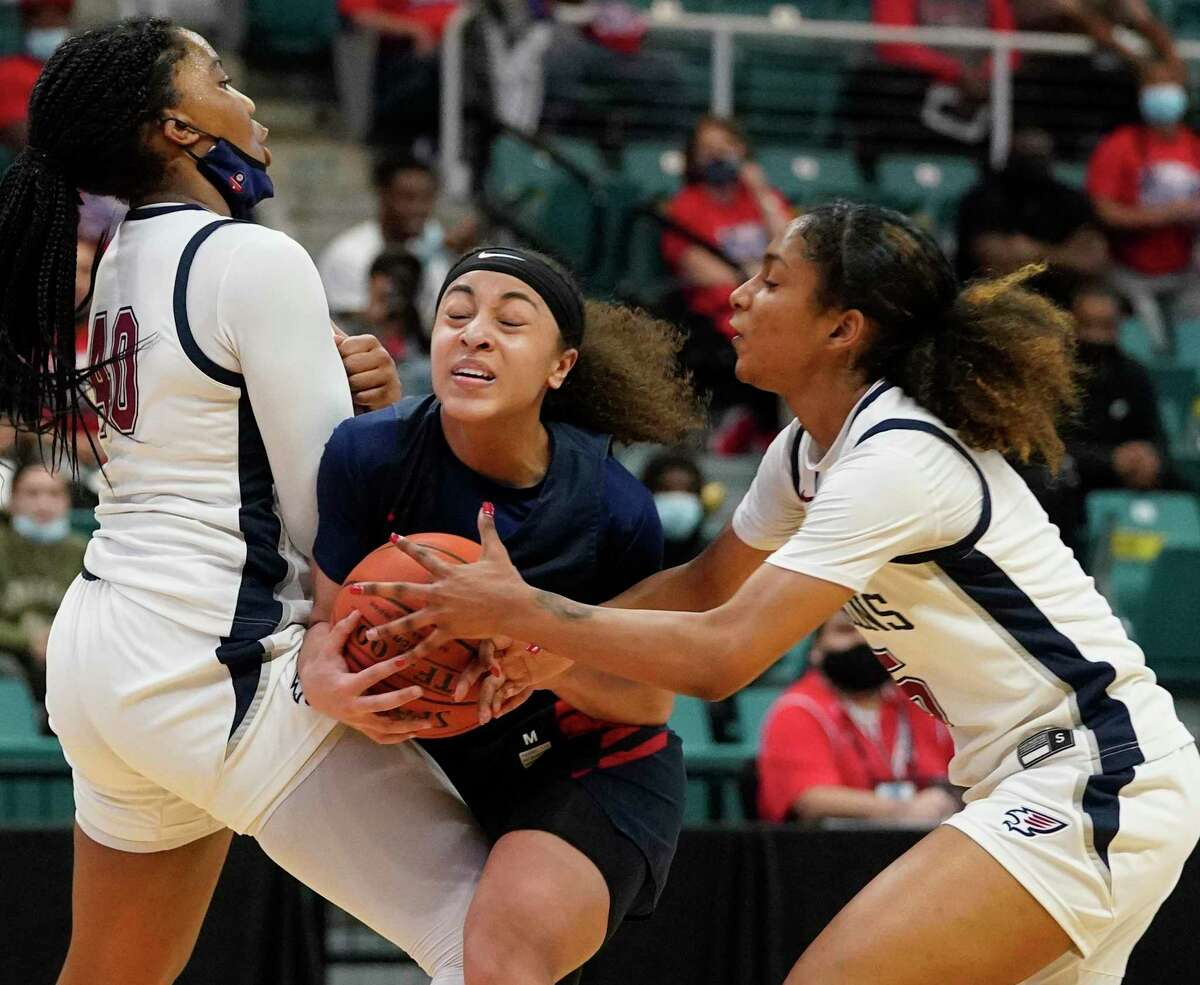 Dulles Nya Threatt (11) is surrounded by Tompkins Ashley Ngene (40) and Crystal Smith (5) during girls basketball playoff game at the Merrell Center last month.