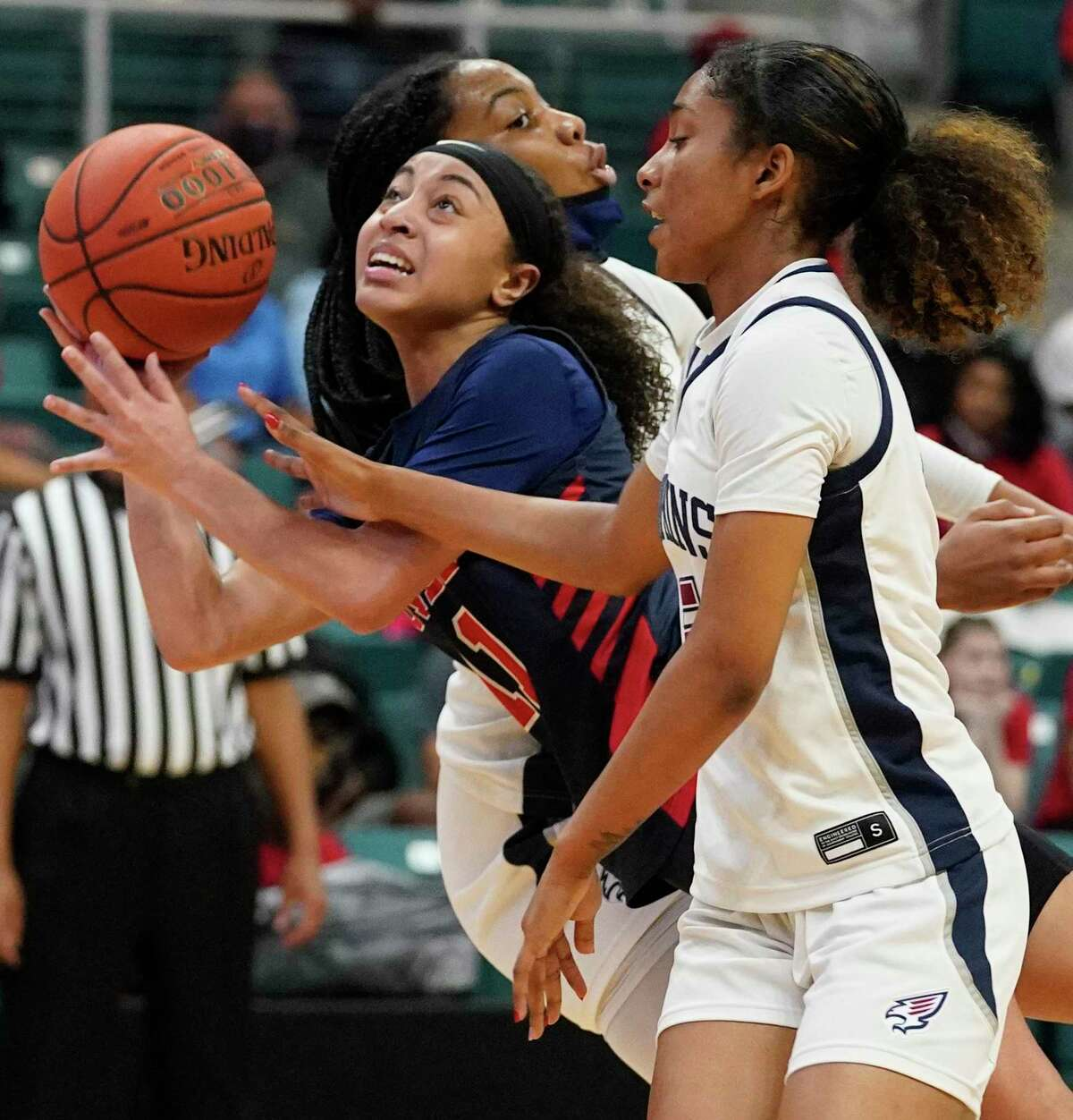 Dulles Nya Threatt (11) is fouled by Tompkins Crystal Smith (5) during girls basketball playoff game at the Merrell Center Wednesday, Feb. 24, 2021 in Katy.