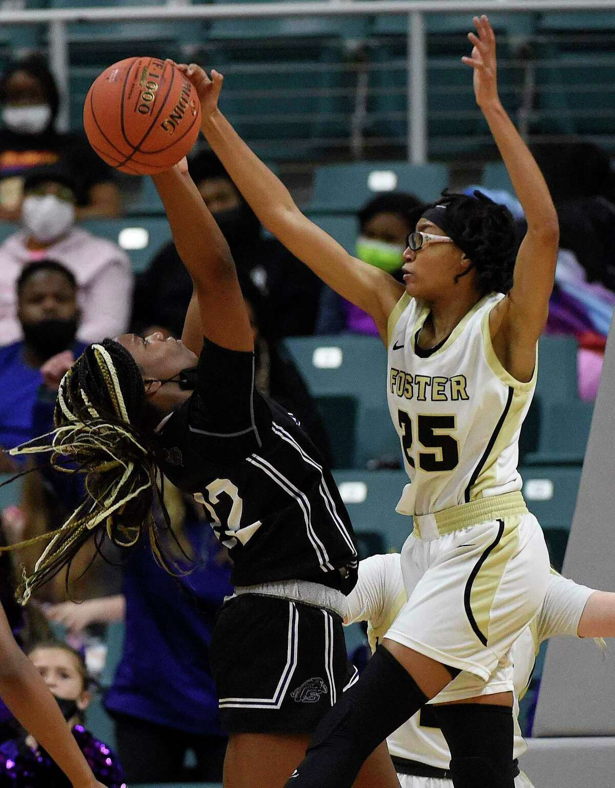 Foster's Imani Avery, right, blocks the shot of College Station's Jayden Davenport during the second half of a 5A Region III semifinal high school basketball playoff game, Friday, Feb. 26, 2021, in Katy, TX.