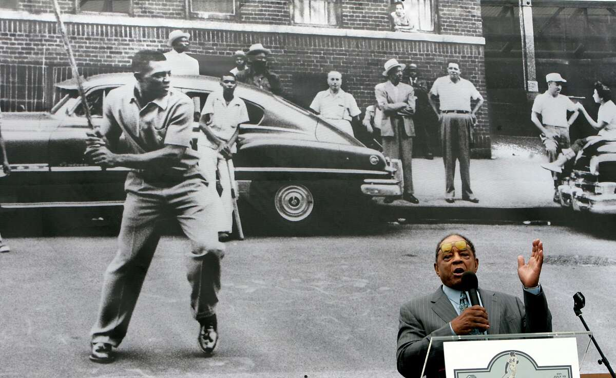 With a photo of Willie Mays in his younger days playing stick ball in Harlem in the background, Mays speaks at a dedication of the Willie Mays Boys & Girls Club at Hunters Point.