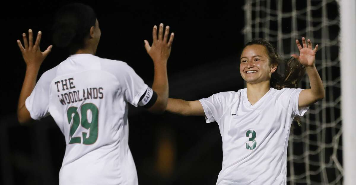 The Woodlands forward Katherine Williams (3) celebrates her third goal of the second period with forward Samone Knight (29) during a District 13-6A high school soccer match at College Park High School, Friday, March 19, 2021, in The Woodlands.
