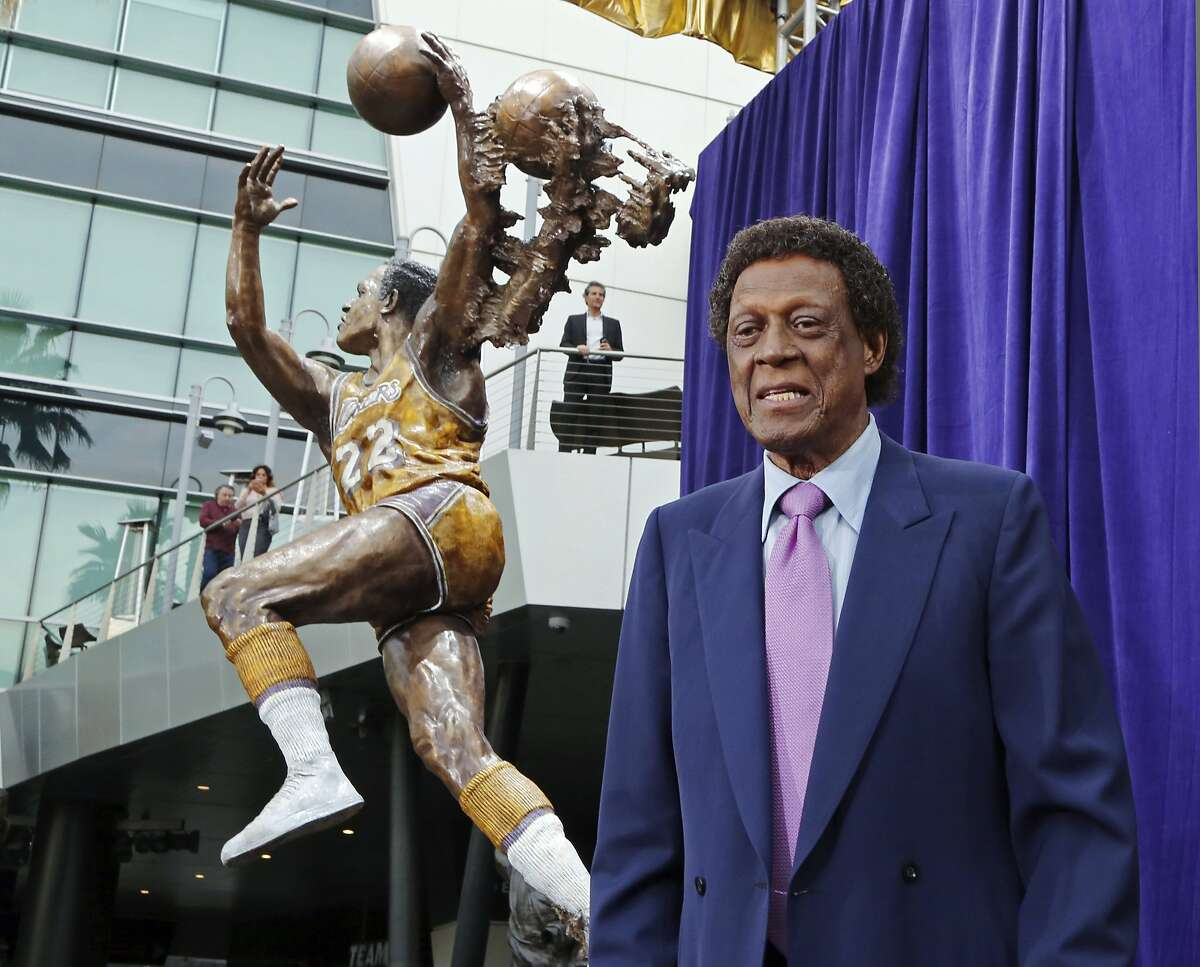 Lakers great and Hall of Famer Elgin Baylor stands next to a statue honoring him outside Staples Center in L.A. in 2018.