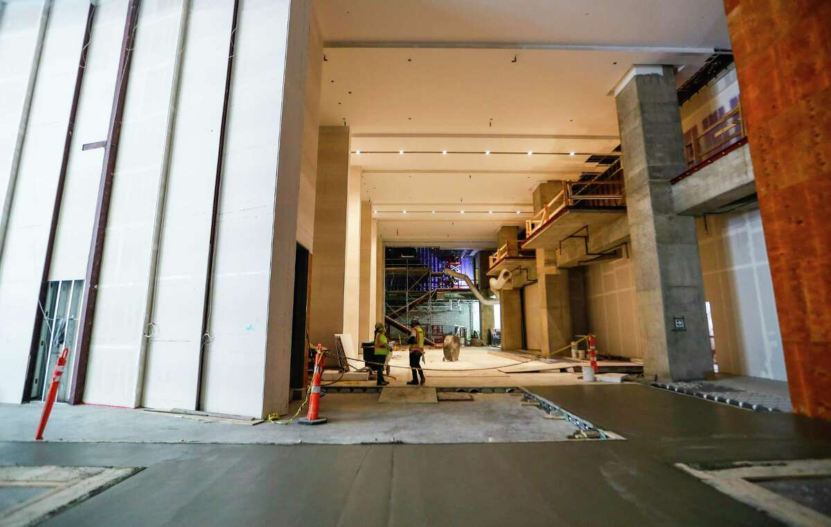 Workers walk across the lobby area inside the 47-story Texas Tower office building at 845 Texas Ave. in downtown Houston after a topping out ceremony, Monday, March 22, 2021. The building, designed by Pelli Clarke Pelli, is a development of Hines and Ivanhoé Cambridge. Hines hoisted an evergreen tree to signal completion of the framing of the structure and wish luck for the future of the building project and its eventual occupants.
