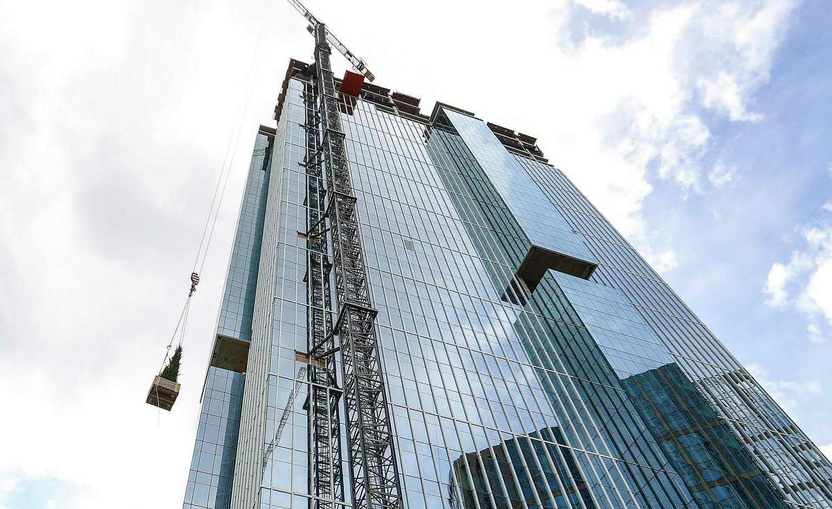An evergreen tree ascends the 47-story Texas Tower office building at 845 Texas Ave. in downtown Houston during a topping out ceremony in March. The building, designed by Pelli Clarke Pelli, is a development of Hines and Ivanhoé Cambridge.
