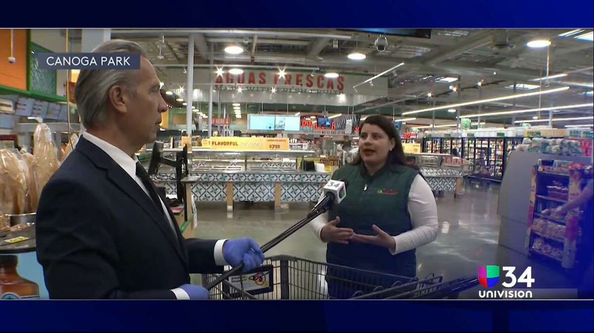 Univision's Oswaldo Borraez uses a long microphone to interview a grocery store customer, one of many adaptations newscasters have made due to the coronavirus outbreak.