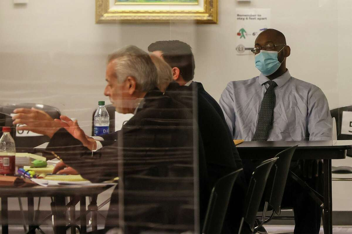 Otis McKane, right, sits with his defense attorneys during individual jury selection Monday, March 22, 2021. McKane is accused of killing San Antonio Police Detective Benjamin Marconi in front of Public Safety Headquarters while the officer was writing a traffic ticket in his SUV on Nov. 20, 2016.