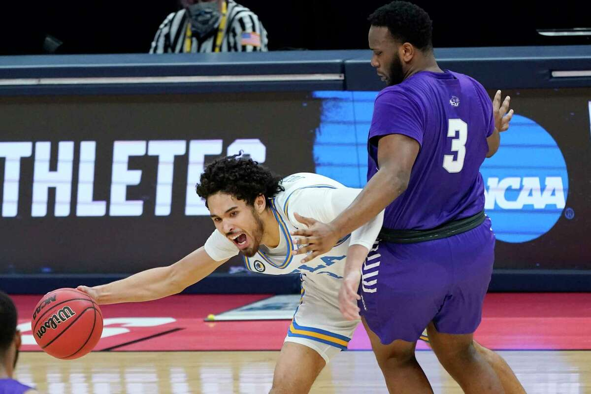 UCLA's Johnny Juzang, left, tries to get past Abilene Christian's Airion Simmons (3) during the first half of a college basketball game in the second round of the NCAA tournament at Bankers Life Fieldhouse in Indianapolis Monday, March 22, 2021.