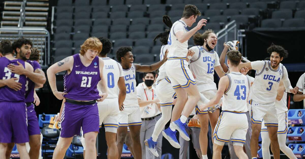 The UCLA Bruins celebrate their win over the Abilene Christian Wildcats in the second round game of the 2021 NCAA Men's Basketball Tournament at Bankers Life Fieldhouse on March 22, 2021 in Indianapolis, Indiana. (Photo by Sarah Stier/Getty Images)