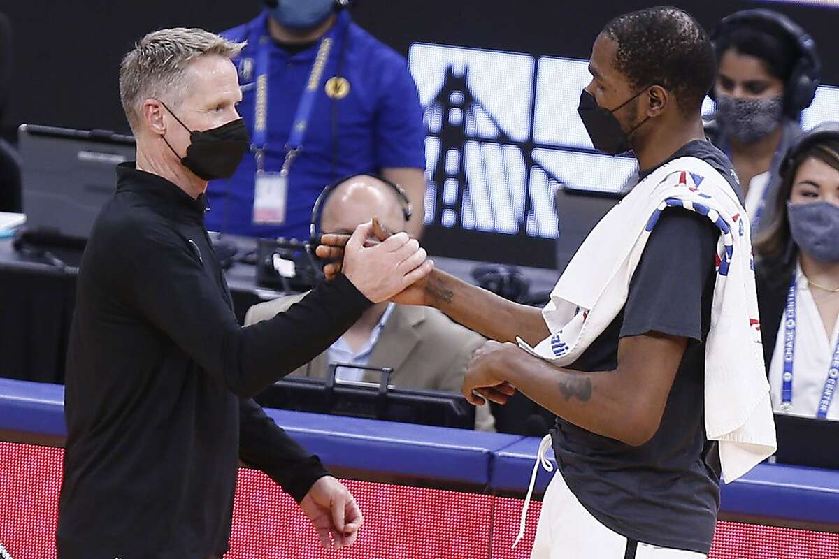Golden State Warriors head coach Steve Kerr (left) and Brooklyn Nets forward Kevin Durant embrace and chat after the NBA game at Chase Center, Saturday, Feb. 13, 2021, in San Francisco, Calif. The Nets won 134-117.