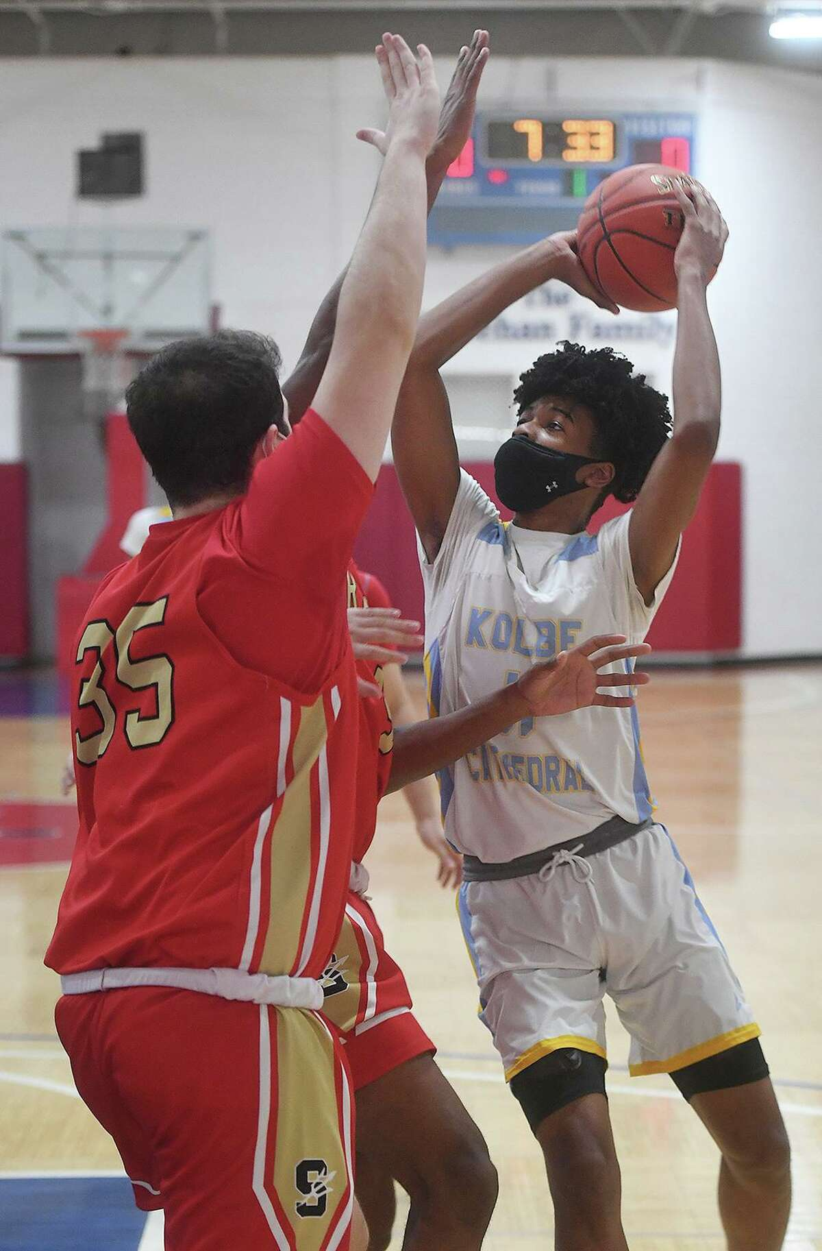 Kolbe Cathedral's Michael Olivencia drives to the basket against two Stratford defenders during the first half of the SWC tournament semifinals at the Cardinal Sheehan Center in Bridgeport, Conn. on Monday, March 22, 2021.